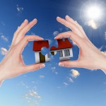 Human hand against blue sky background and house